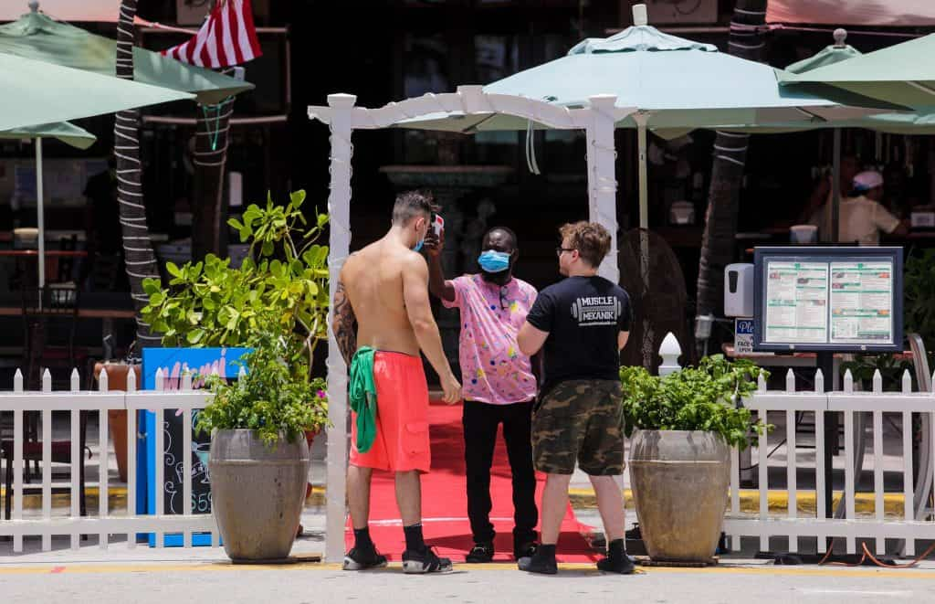 A restaurant employee checked the temperatures of customers on Sunday in Miami Beach, Fla.Credit...Saul Martinez for The New York Times
