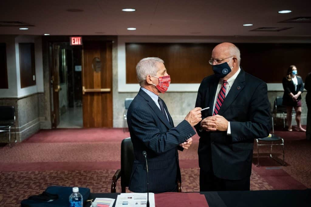 """""""Wearing a face covering is a critically important tool,"""" said Dr. Robert Redfield, right, director of the Centers for Disease Control and Prevention.Credit...Pool photo by Al Drago"""